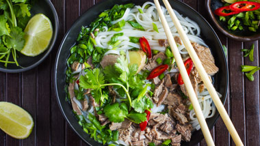 beef pho on wooden background with limes and cilantro